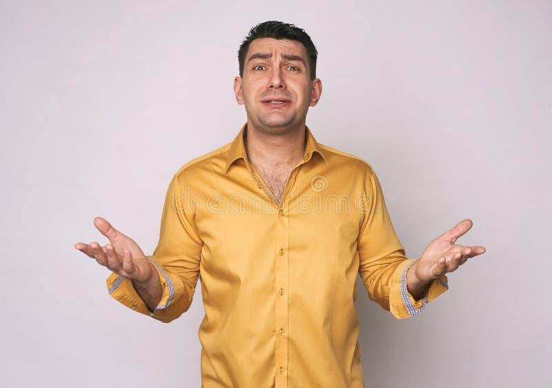 Frustrierter Mann im gelben Hemd lokalisiert lizenzfreie stockfotos