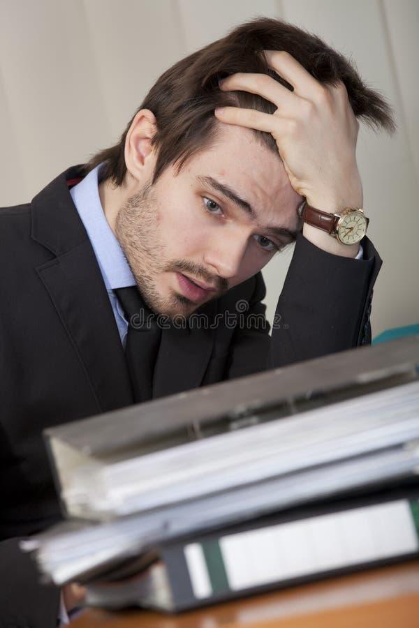 Frustrierter Mann mit Faltblättern stockfotografie
