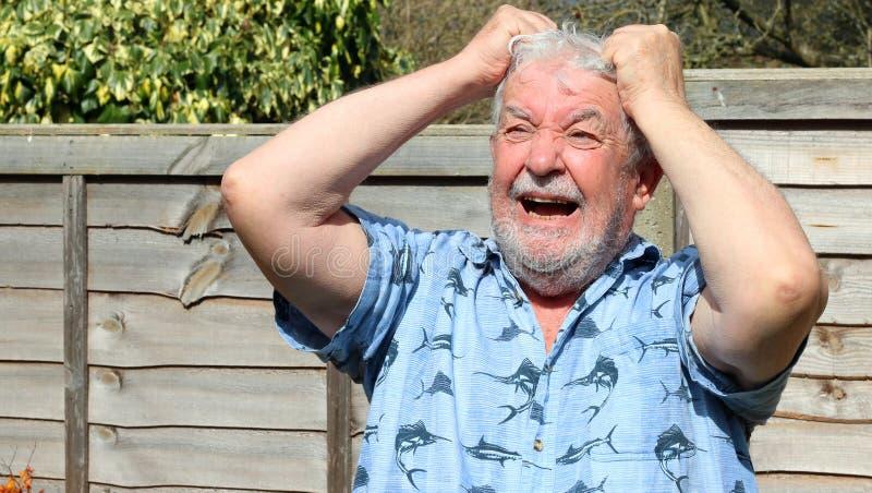 Frustrierter und verärgerter älterer Mann, der sein Haar zieht stockfotografie