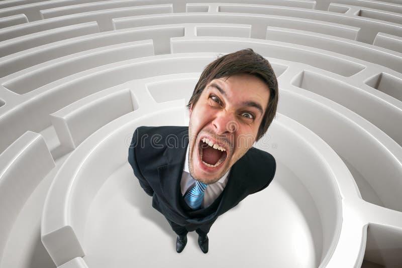 Frustrierter verärgerter Mann ist im Labyrinth verloren 3D übertrug Illustration des Labyrinths stockfotografie