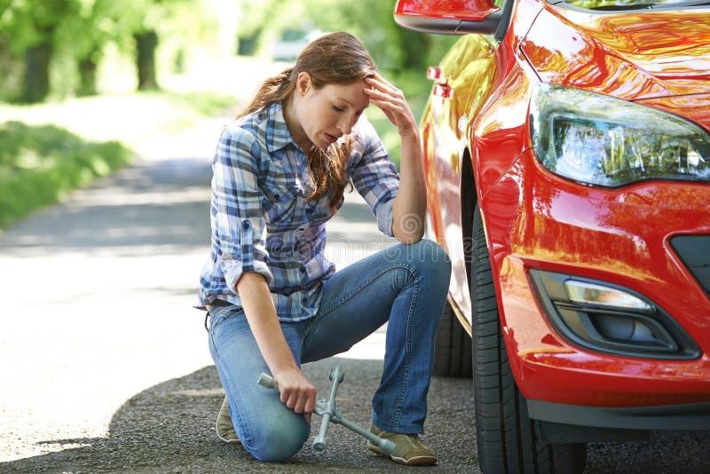 Frustrierter weiblicher Fahrer With Tyre Iron, das zum Änderungs-Rad versucht lizenzfreies stockfoto