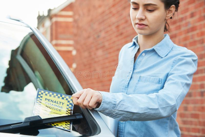 Frustrierter weiblicher Kraftfahrer, der Strafzettel betrachtet stockbilder