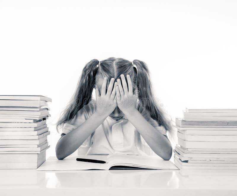 Frustriertes kleines Schulmädchen, das einem Ausfall unfähig, sich in der Lesung zu konzentrieren glaubt und Schwierigkeitslernen lizenzfreies stockbild