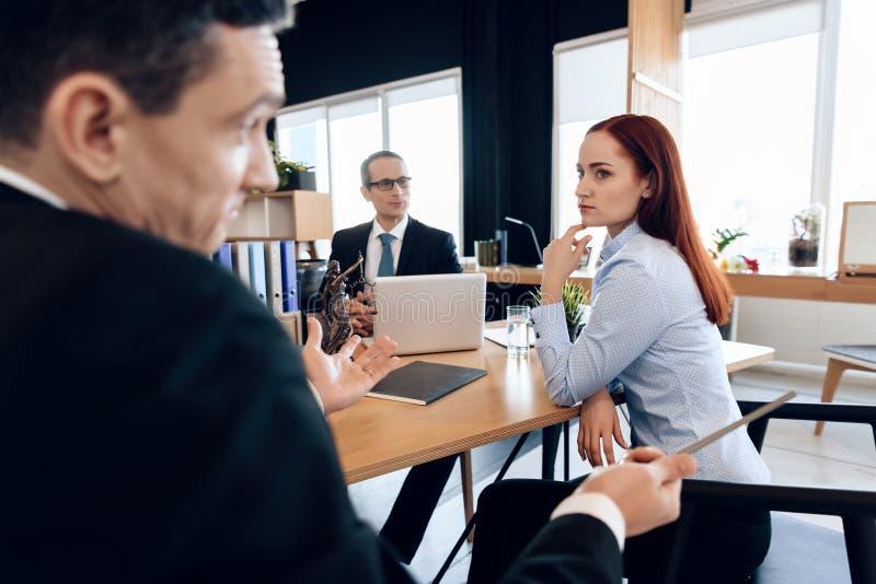 Frustriertes rothaariges Mädchen betrachtet erwachsenen Mann, der ihre Hände im Scheidungsbüro verbreitet lizenzfreie stockfotografie