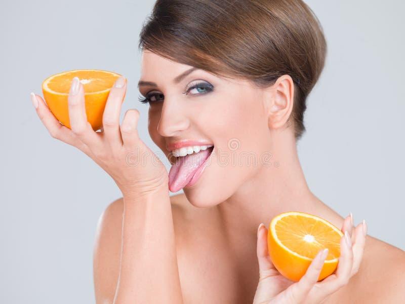 Fruta anaranjada cortada tenencia desnuda sensual de la mujer fotografía de archivo libre de regalías