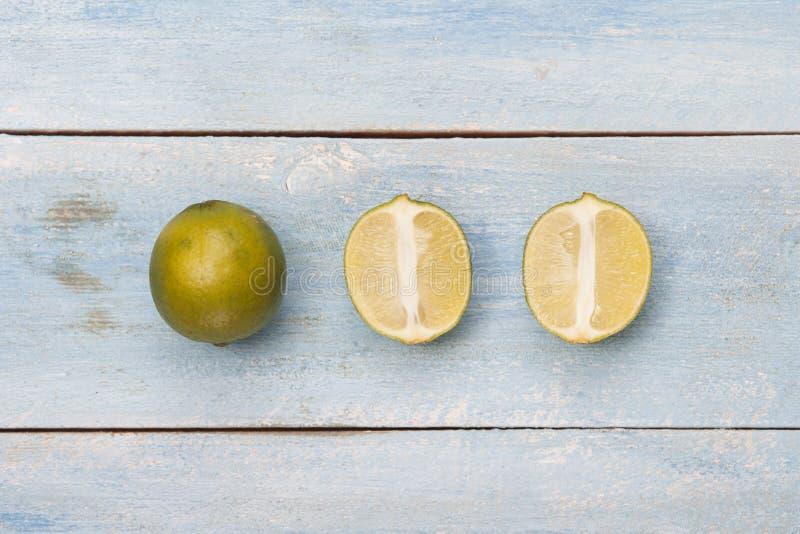 Fruta cítrica en un viejo tablero de madera azul Opinión superior de la cal fotos de archivo