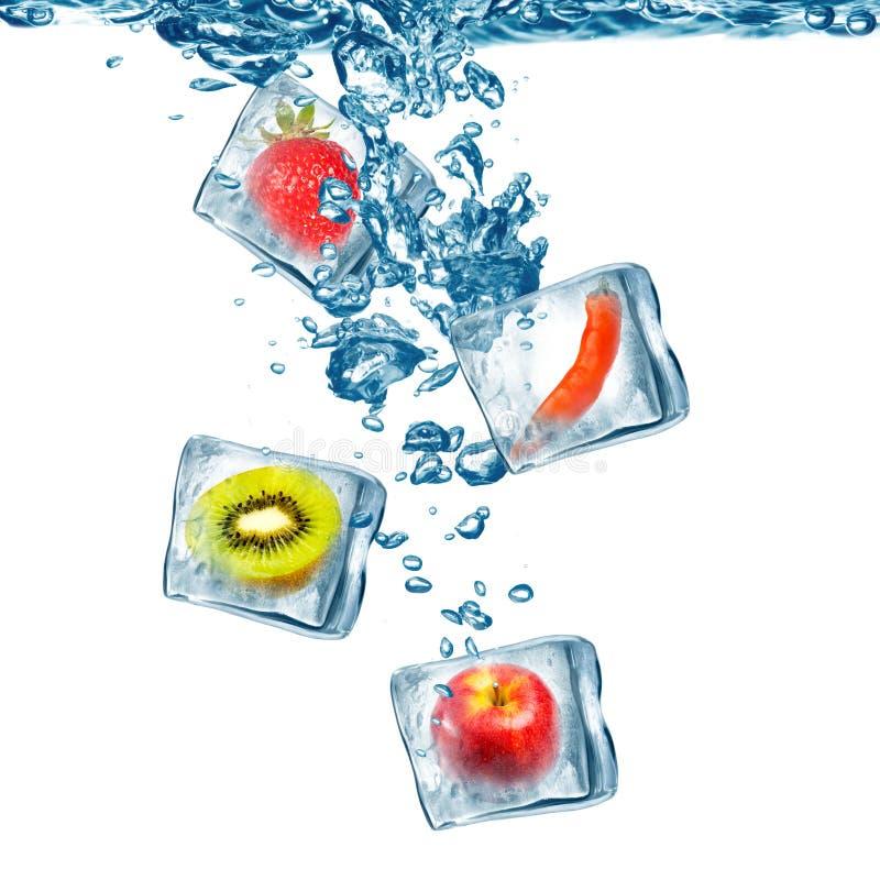 Fruta congelada en gota del cubo de hielo en el agua foto de archivo