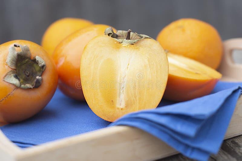 fruta de color caqui fresca aislada, cortado por la mitad, en la tabla r?stica Alimento sano fotos de archivo