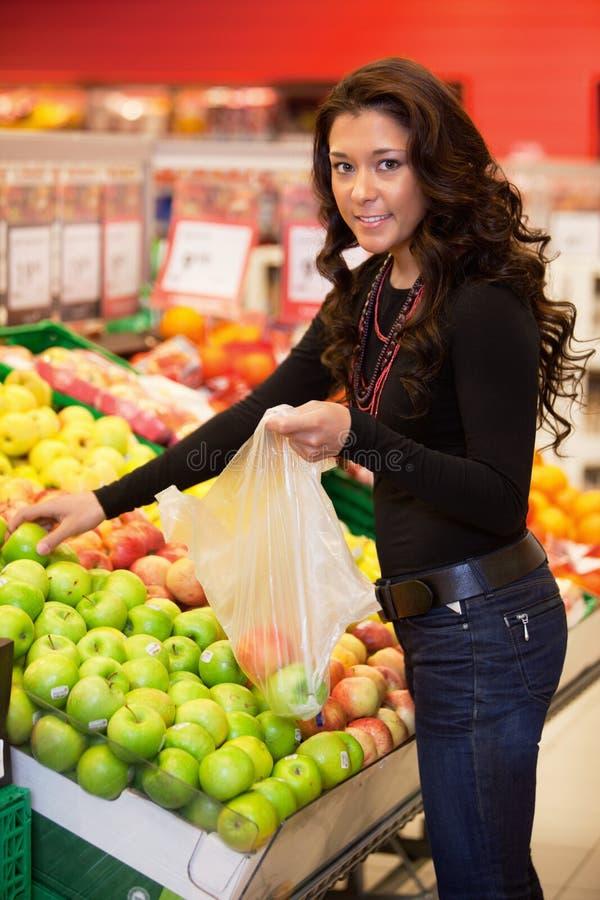 Fruta de compra de la mujer joven imágenes de archivo libres de regalías