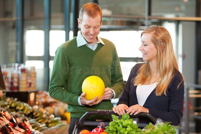 Fruta de compra del hombre y de la mujer fotografía de archivo libre de regalías