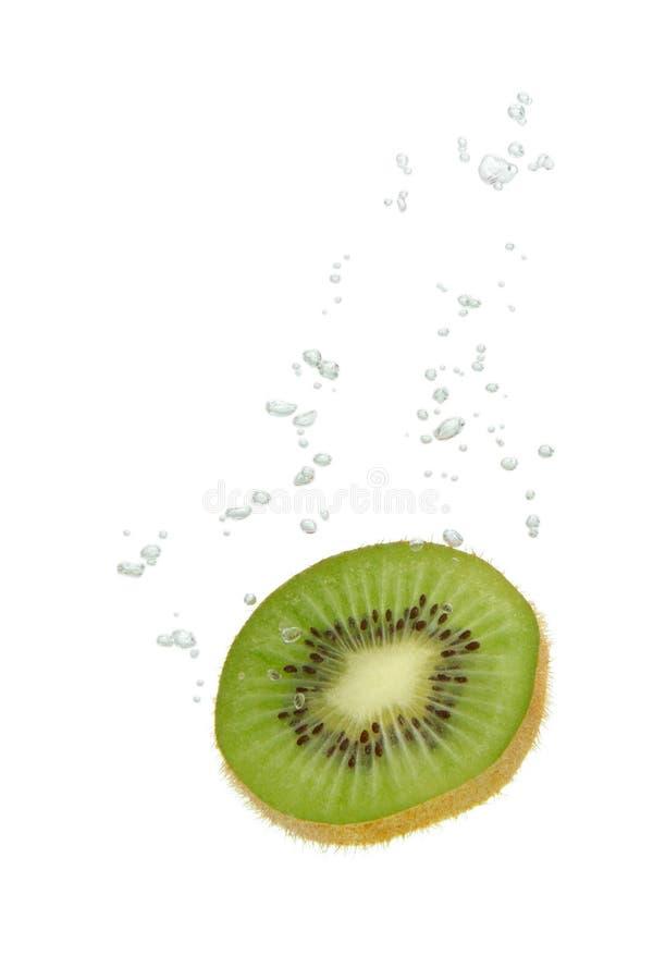 Fruta de kiwi en agua con las burbujas de aire foto de archivo libre de regalías