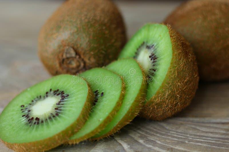 Fruta de kiwi madura, jugoso, corte en los pedazos aislados en fondo marrón de madera imagenes de archivo