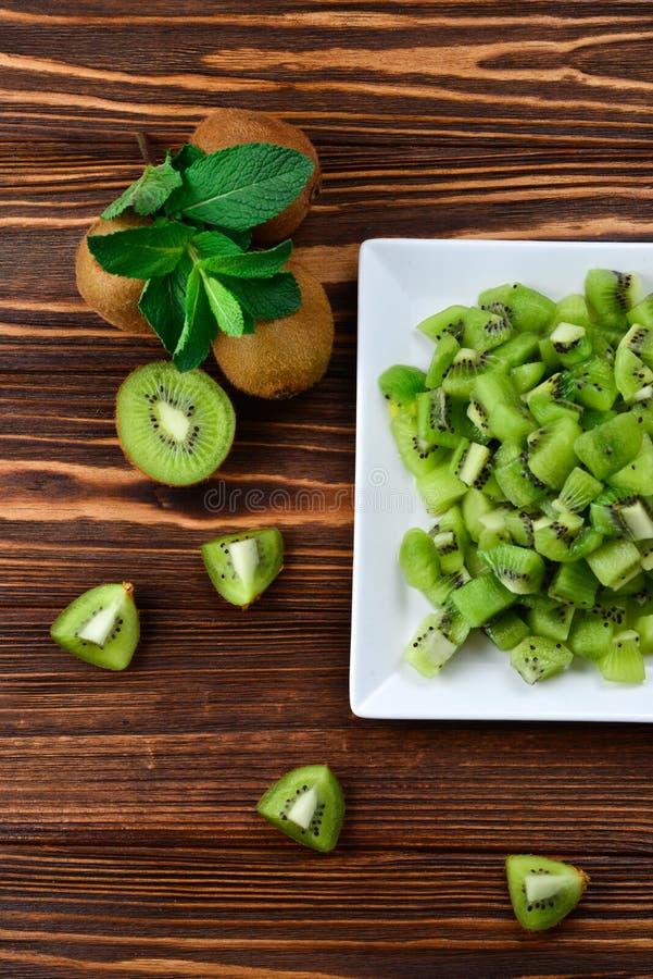 Fruta de kiwi recientemente cortada con los kiwis enteros imagen de archivo