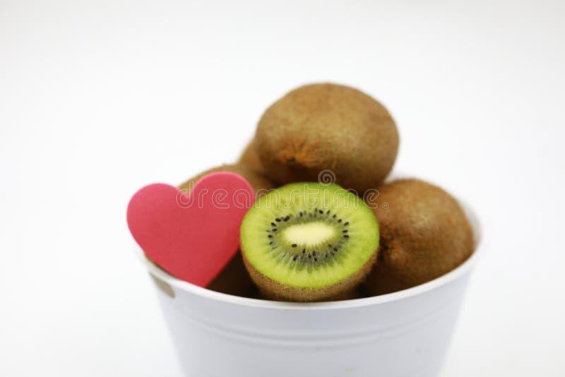 Fruta de kiwi y amor rojo en cuenco imagenes de archivo