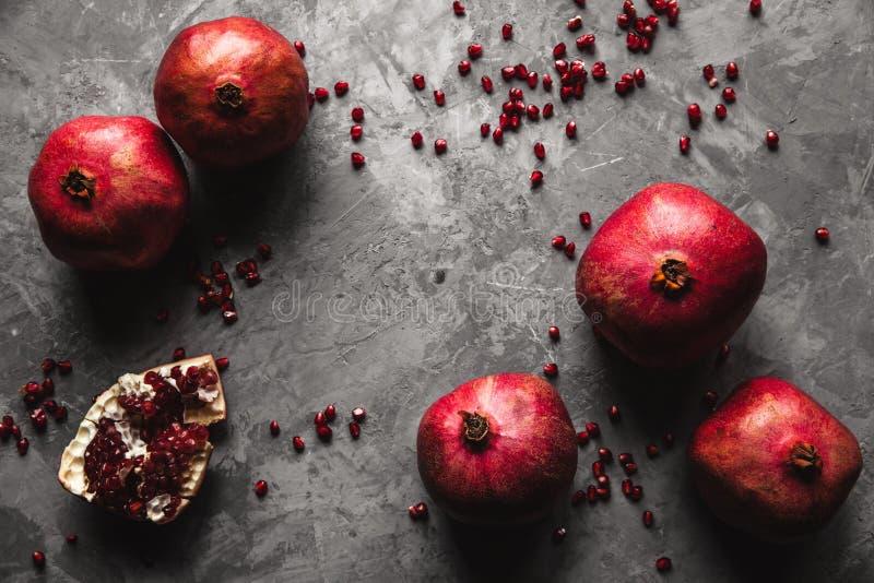 Fruta de la granada Granada madura y jugosa en fondo gris rústico con el espacio de la copia para su texto fotografía de archivo libre de regalías