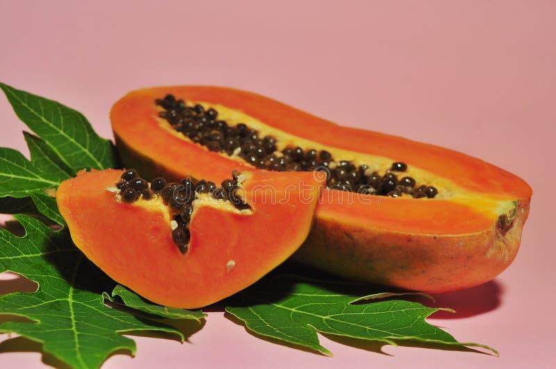 Fruta de la papaya aislada en fondo rosado fotografía de archivo