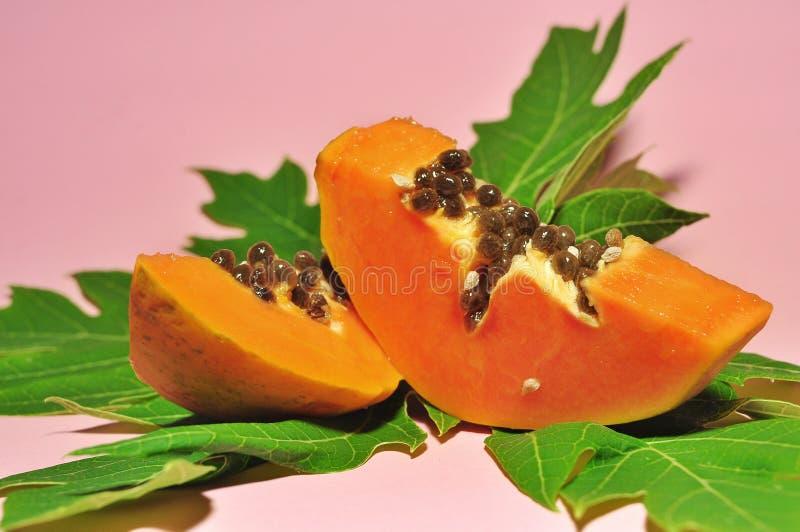 Fruta de la papaya aislada en fondo rosado imagen de archivo