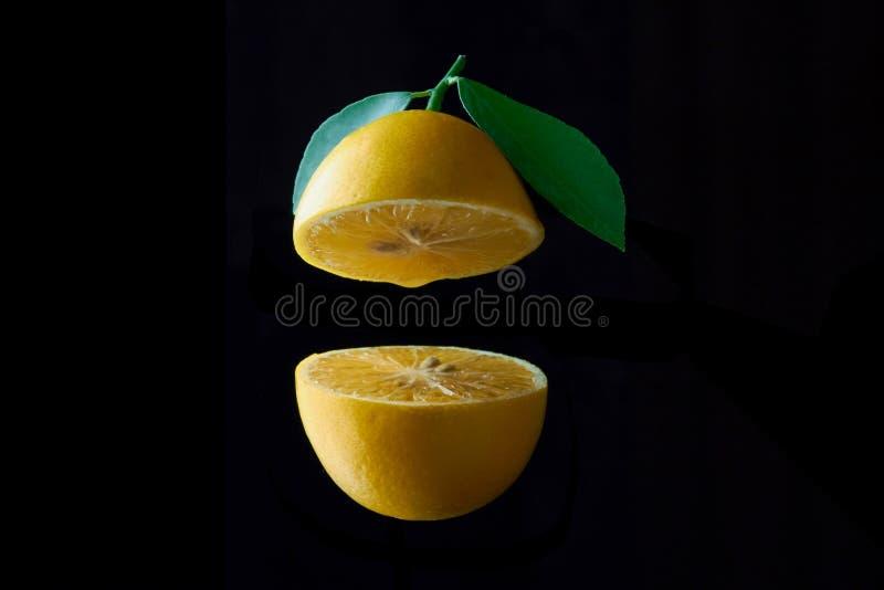Fruta del limón con la hoja aislada en fondo negro imagenes de archivo