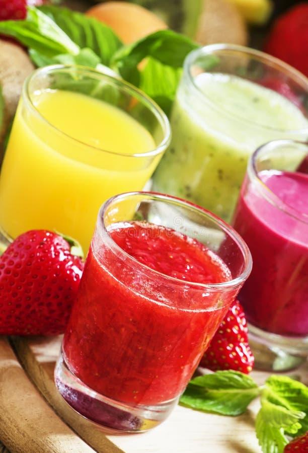 Fruta del verano y jugos y smoothies coloridos de la baya en vidrios: imagen de archivo