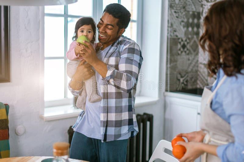 Fruta eathing de la niña mientras que siendo control en los brazos de su papá fotos de archivo libres de regalías