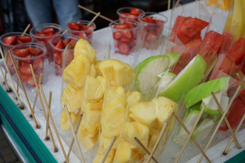 Fruta, fresa, sandía y piña cortadas frescas en paquete preparado en el vendedor de la parada de calle imágenes de archivo libres de regalías