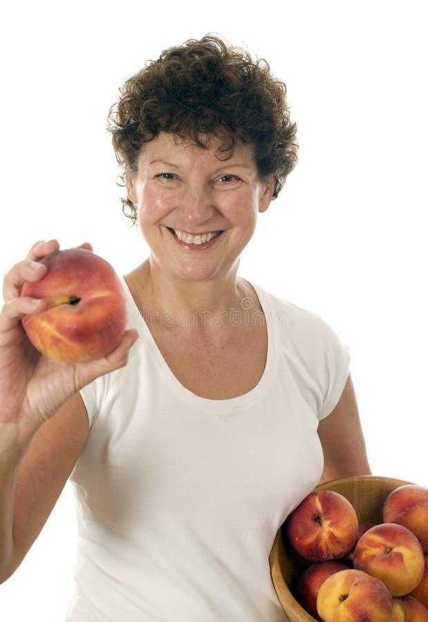 fruta fresca de los melocotones de la mujer mayor imágenes de archivo libres de regalías