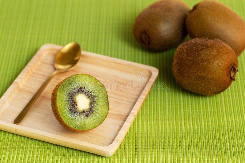 Fruta kiwi abierta en un plato cuadrado de madera sobre un fondo de alfombra verde fotos de archivo libres de regalías