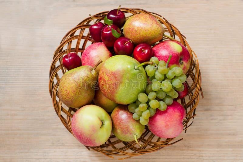 Fruta madura fresca - manzanas, peras, uvas y ciruelos en una placa de madera de mimbre en una tabla de madera Visión superior Co foto de archivo libre de regalías