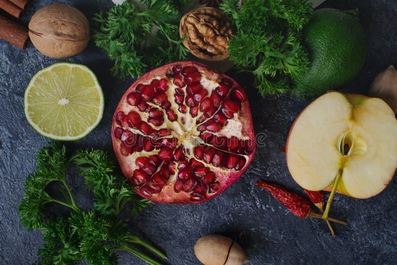 Fruta orgánica cruda, verde, verduras y nueces en la tabla de piedra oscura foto de archivo