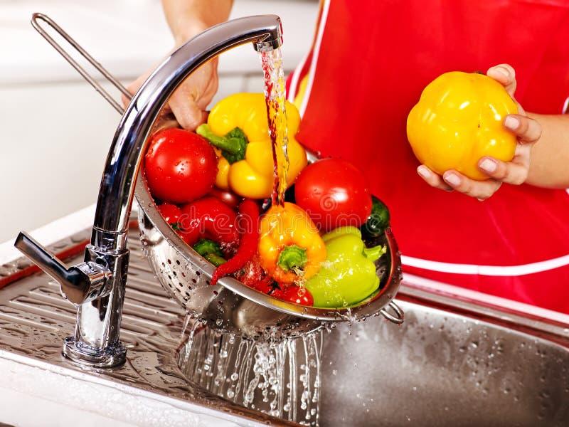 Fruta que se lava de la mujer en la cocina imagen de archivo libre de regalías