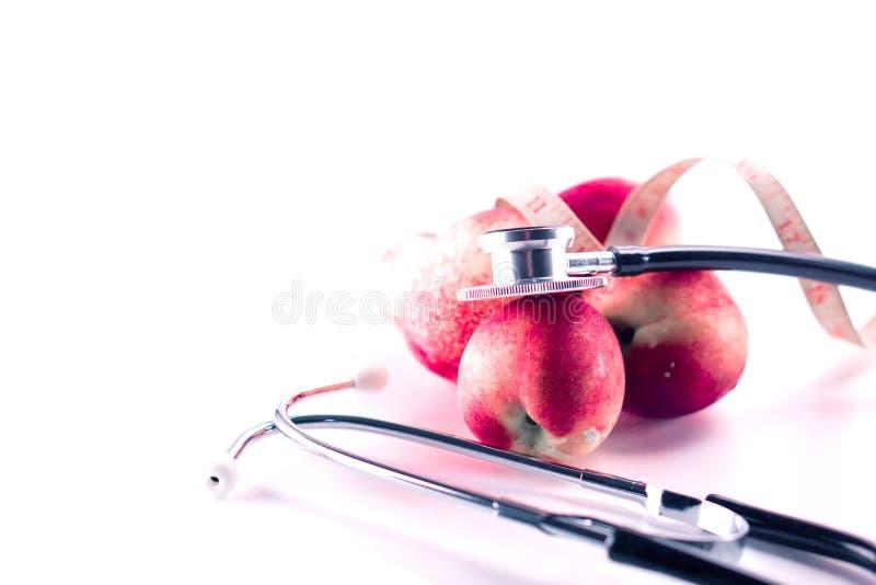 Fruta roja de la nectarina con el estetoscopio auscultating en el fondo blanco imagen de archivo