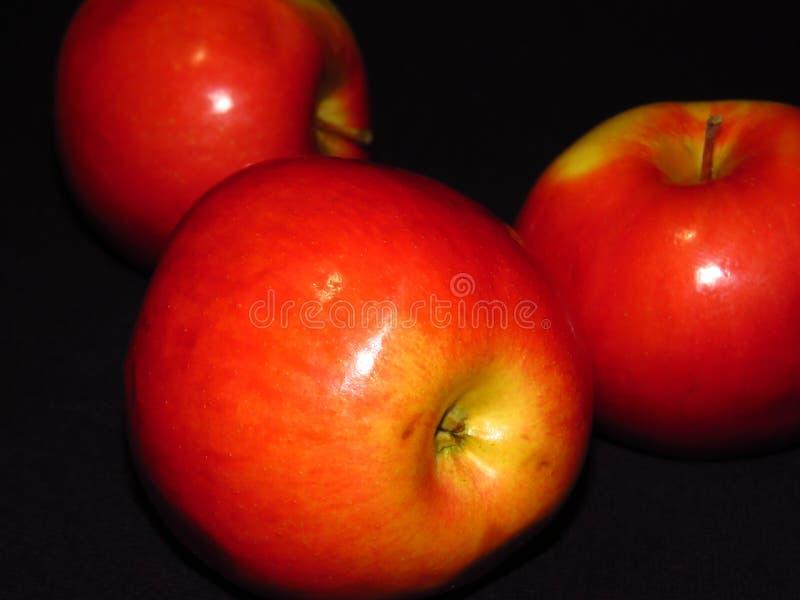 Fruta sana orgánica natural Ciérrese para arriba de tres manzanas jugosas rojas maduras en fondo negro imagen de archivo