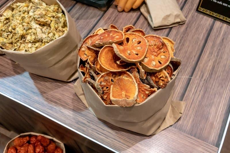 Fruta secada artificial del bael en saco del papel del arte en fondo de madera foto de archivo