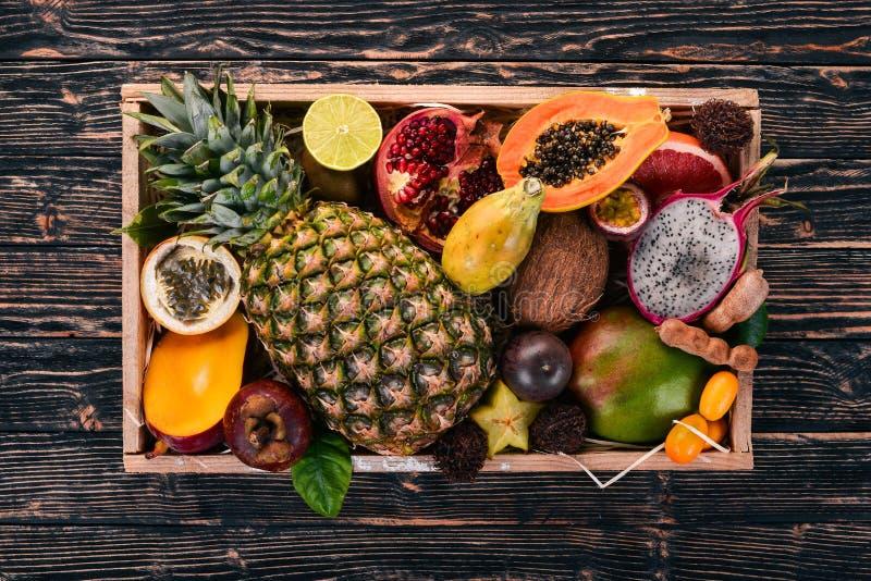 Fruta tropical en una caja de madera Papaya, Dragon Fruit, rambutan, tamarindo, fruta del cactus, aguacate, granadilla, carambola foto de archivo