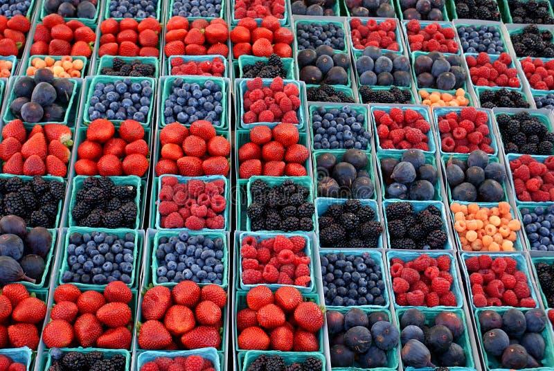 Fruta y bayas coloridas en un mercado al aire libre fotos de archivo