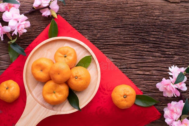 Fruta y flor de cerezo anaranjadas en la tabla de madera, fondo chino de la celebración del Año Nuevo foto de archivo libre de regalías