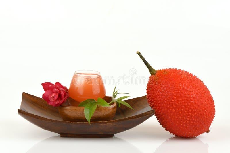 Fruta y jugo de Gac en el fondo blanco foto de archivo libre de regalías