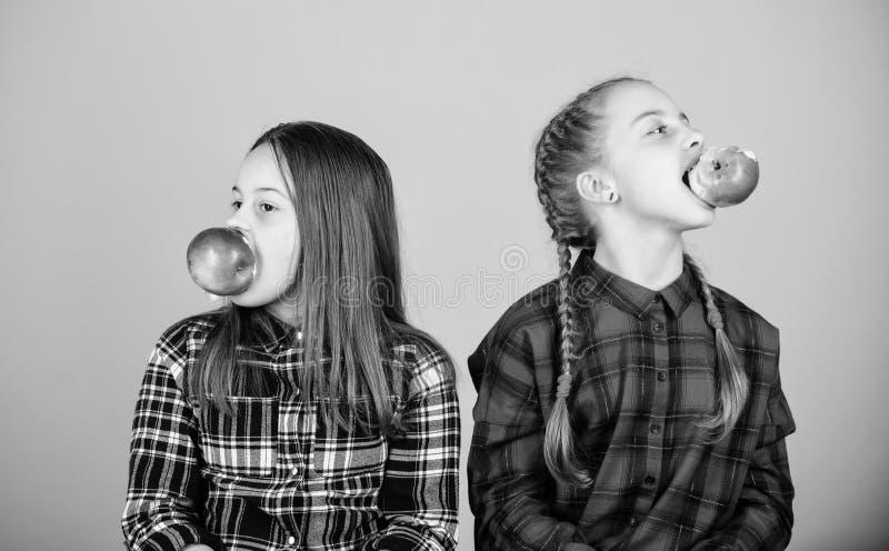 Fruta, fruta y más fruta Niñas que comen las frutas frescas Pequeñas muchachas que sostienen manzanas en bocas Ni?os lindos foto de archivo