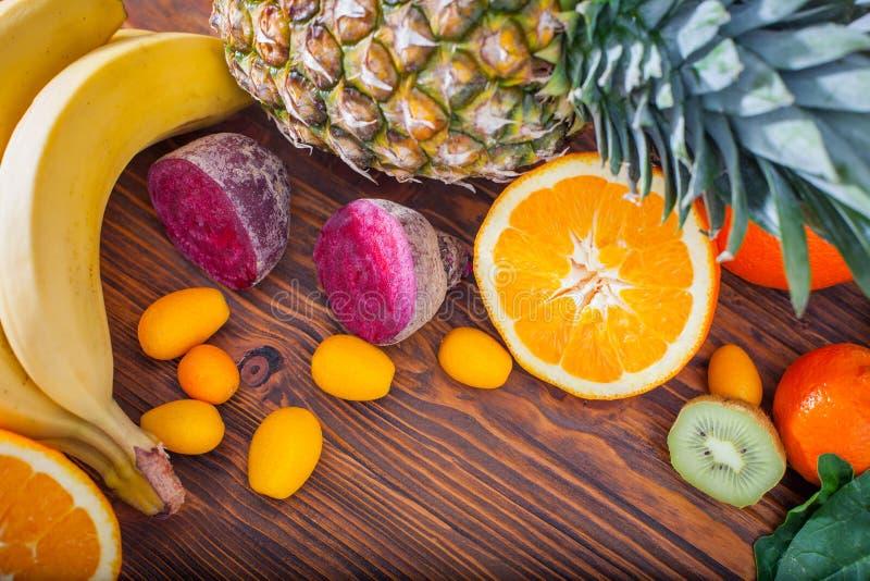 Fruta y verdura fresca en la tabla de madera imagenes de archivo