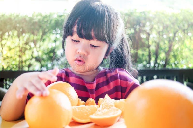 Fruta y verdura para el concepto de los niños Poca muchacha linda de los años 3-4 con la naranja cortada en la placa de madera fotos de archivo libres de regalías