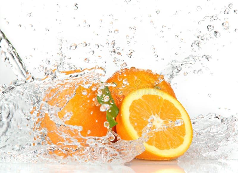 Frutas alaranjadas com espirro da água imagens de stock royalty free