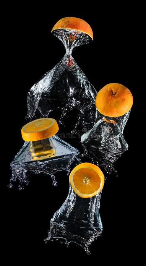 Frutas anaranjadas droping de la rebanada del agua imagenes de archivo