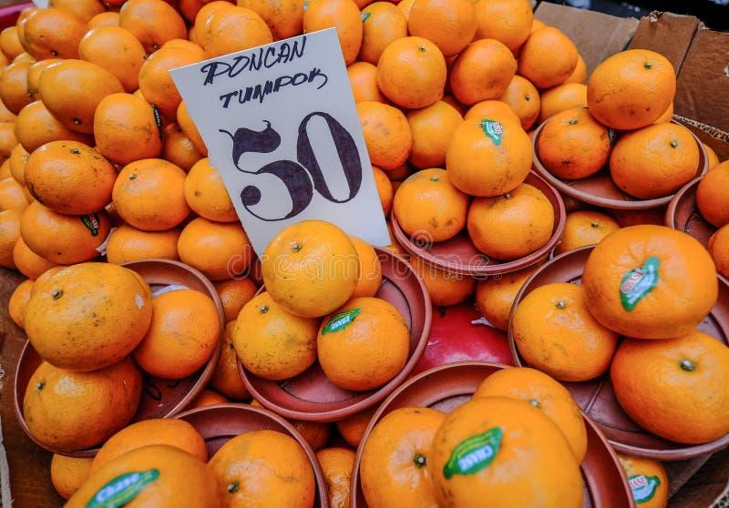 Frutas anaranjadas en venta en el mercado local foto de archivo libre de regalías
