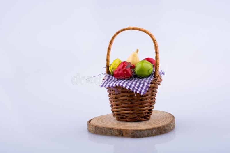 Frutas artificiales en la cesta de mimbre aislada en el fondo blanco imagenes de archivo