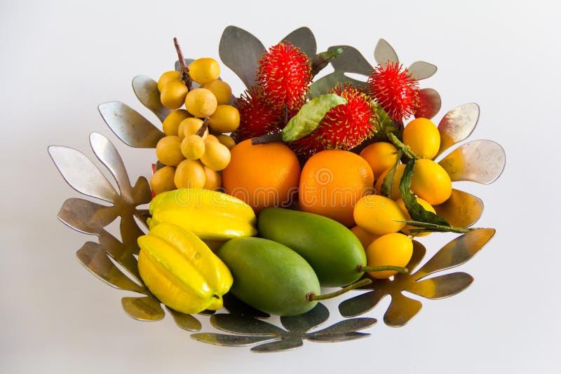 Frutas artificiales en la cesta en el fondo blanco para el decorati imagenes de archivo