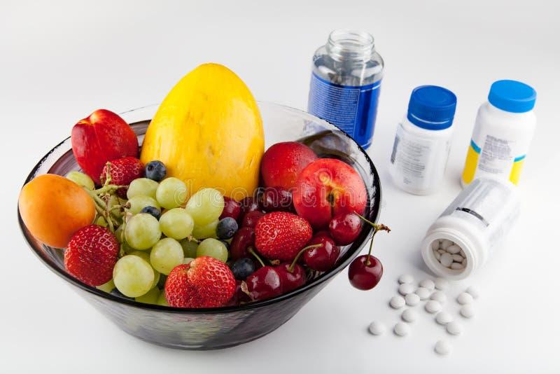 Frutas contra píldoras foto de archivo