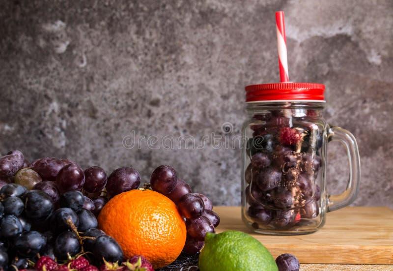 Frutas de la forma del tarro del Smoothie Uvas, frambuesa, cal, fondo oscuro foto de archivo libre de regalías