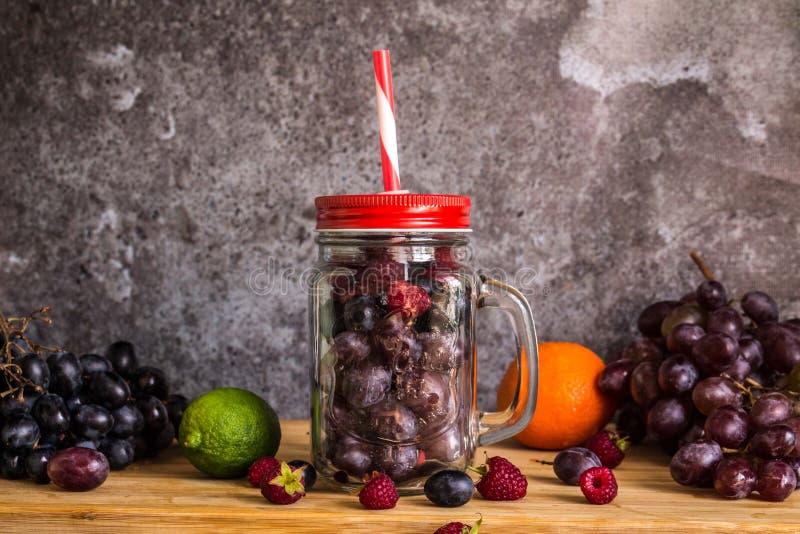 Frutas de la forma del tarro del Smoothie Uvas, frambuesa, cal, fondo oscuro fotografía de archivo libre de regalías