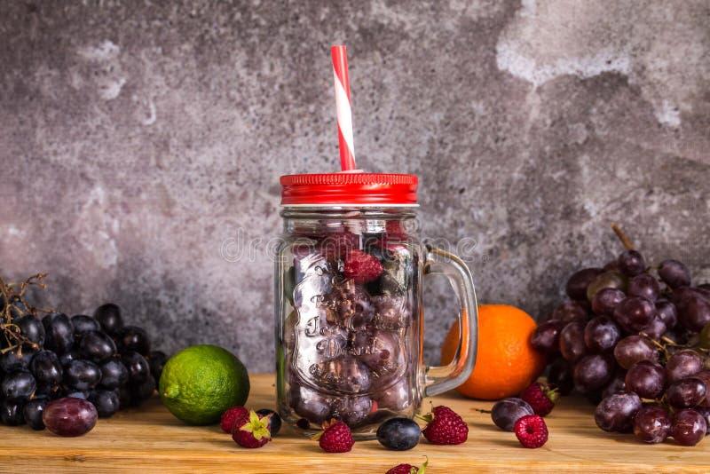 Frutas de la forma del tarro del Smoothie Uvas, frambuesa, cal, fondo oscuro imagen de archivo