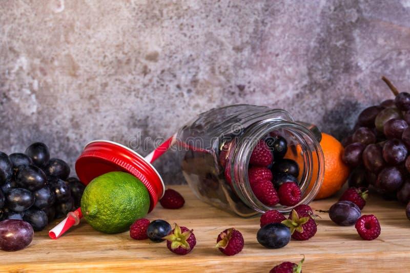 Frutas de la forma del tarro del Smoothie Uvas, frambuesa, cal, fondo oscuro imagen de archivo libre de regalías